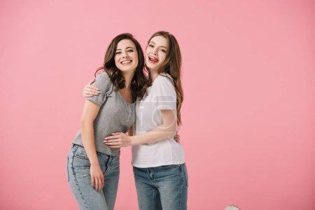 Photo pour Femmes attirantes et souriantes dans des t-shirts étreignant d'isolement sur le rose - image libre de droit