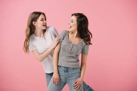 Photo pour Femmes attirantes et souriantes dans des t-shirts regardant l'un l'autre isolé sur le rose - image libre de droit