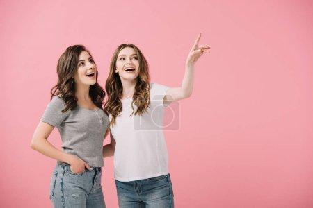 Photo pour Femmes attirantes et souriantes dans des t-shirts pointant avec le doigt isolé sur le rose - image libre de droit
