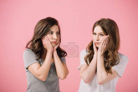 Photo pour Femmes attirantes et tristes dans des t-shirts regardant loin isolés sur le rose - image libre de droit