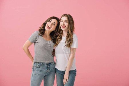 Photo pour Femmes attirantes et souriantes dans des t-shirts avec collant des langues regardant l'appareil-photo isolé sur le rose - image libre de droit