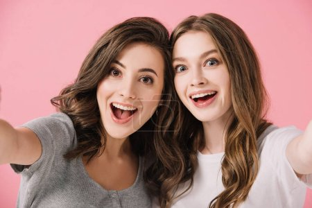 Photo for Attractive and shocked women in t-shirts looking at camera isolated on pink - Royalty Free Image