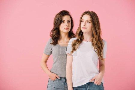 Photo pour Femmes attirantes dans des t-shirts regardant loin isolés sur le rose - image libre de droit