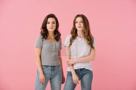 Photo pour Femmes attirantes dans des t-shirts regardant l'appareil-photo isolé sur le rose - image libre de droit