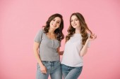 attractive and smiling women in t-shirts looking at camera isolated on pink