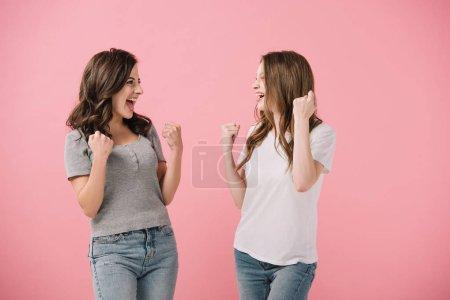 Photo pour Femmes attirantes et souriantes dans des t-shirts affichant des gestes de oui isolés sur le rose - image libre de droit