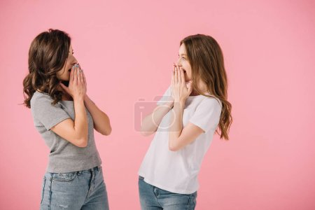 Photo for Attractive and shocked women in t-shirts looking at each other isolated on pink - Royalty Free Image
