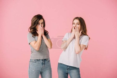 Photo pour Femmes attirantes et choquées dans des t-shirts regardant l'appareil-photo isolé sur le rose - image libre de droit