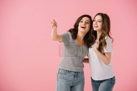 Photo for Attractive and smiling women in t-shirts pointing with finger isolated on pink - Royalty Free Image