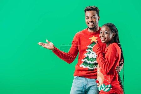 Photo pour Afro-Américain pointant avec la main et regarder la caméra près de la femme en pull de Noël isolé sur vert - image libre de droit