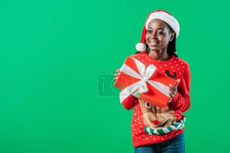 Photo pour Femme afro-américaine en pull de Noël et chapeau de Père Noël tenant présent isolé sur vert - image libre de droit