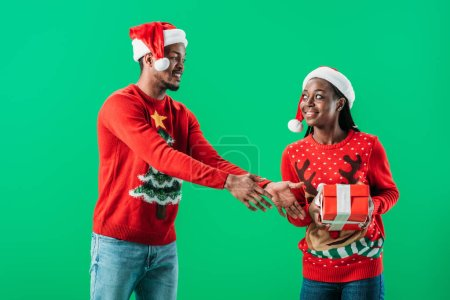 Photo for African American man in red Christmas sweater raising hands to gift box in hands of woman isolated on green - Royalty Free Image