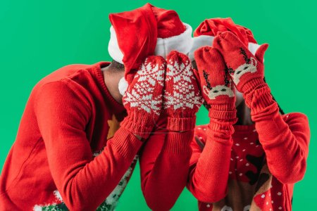Photo pour Couple afro-américain en pulls de Noël et chapeaux de Père Noël couvrant les yeux avec les mains en gants rouges d'hiver avec motif isolé sur vert - image libre de droit