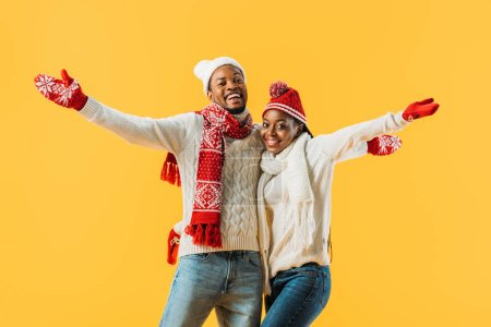 Photo for African American couple in cozy winter outfit hugging, outstretching hands and looking at camera isolated on yellow - Royalty Free Image