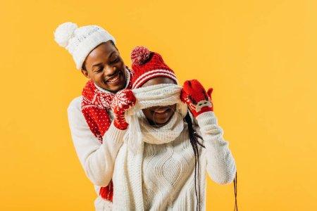 Photo pour Homme d'Afro-américain dans la couverture de tenue d'hiver avec des yeux d'écharpe de femme d'isolement sur le jaune - image libre de droit