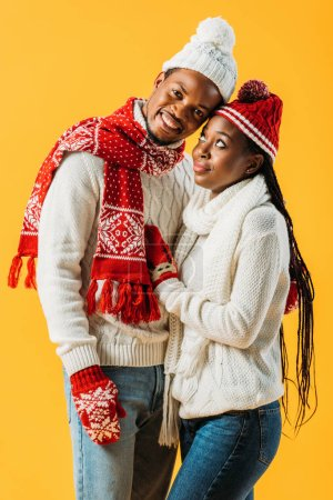 Photo for African American man in winter outfit embracing woman who looking at him isolated on yellow - Royalty Free Image
