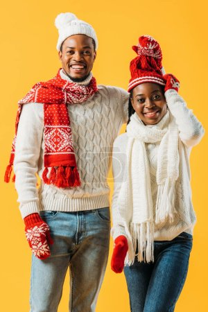 Photo for African American man taking off hat of woman in winter outfit and looking at camera isolated on yellow - Royalty Free Image