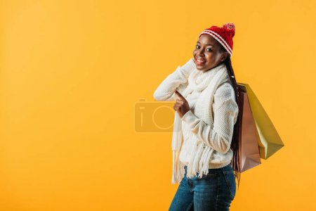 Photo for Side view of African American woman in winter outfit holding shopping bags and pointing with finger isolated on yellow - Royalty Free Image