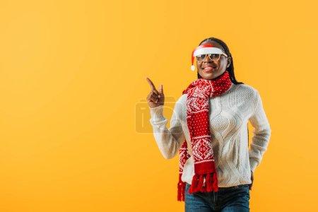 Photo pour Femme d'Afro-américain dans le chandail d'hiver et les glaces de Noel pointant avec le doigt d'isolement sur le jaune - image libre de droit