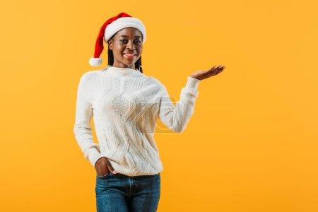 afrikanisch-amerikanische Frau im Winterpullover und Weihnachtsmütze halten Hand in Tasche isoliert auf gelb