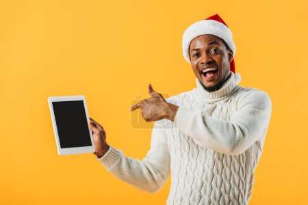 Photo for African American man in Santa hat pointing with finger at digital tablet with blank screen isolated on yellow - Royalty Free Image