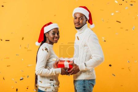 Photo pour Vue de côté de couples afro-américains dans la boîte de cadeau de fixation de Santa sur le fond jaune avec des confettis - image libre de droit