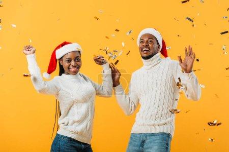 Photo pour Couples afro-américains excités dans des chapeaux de Santa sur le fond jaune avec des confettis - image libre de droit