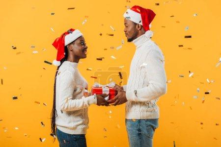 Photo pour Vue de côté du couple d'Afro-américain dans des chapeaux de Santa retenant la boîte de cadeau et regardant l'un l'autre sur le fond jaune avec des confettis - image libre de droit