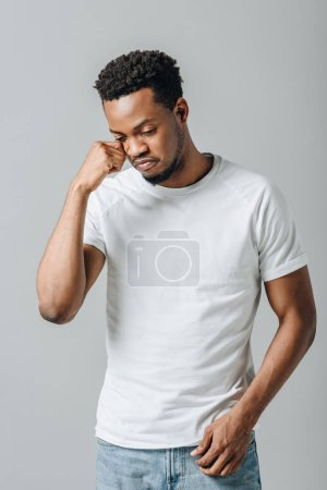 African American man in white T-short crying and looking down isolated on grey