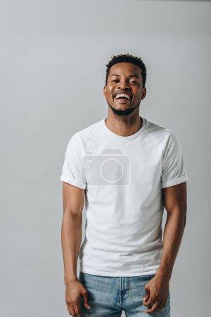 Photo pour Homme d'Afro-américain dans le rire blanc de T-short et regardant la caméra d'isolement sur le gris - image libre de droit
