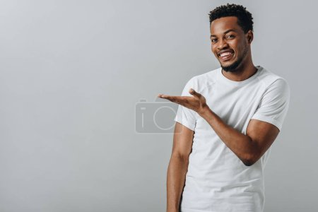 Photo for African American man in white T-short pointing with hand and looking at camera isolated on grey - Royalty Free Image