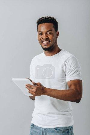 hombre afroamericano feliz sosteniendo la tableta digital y mirando a la cámara aislada en gris
