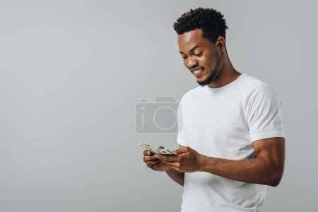 Photo for African American man counting dollar banknotes isolated on grey - Royalty Free Image