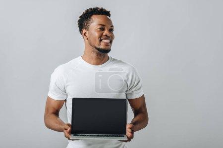 Photo pour Homme d'Afro-américain souriant et affichant l'ordinateur portatif avec l'écran blanc et regardant loin isolé sur le gris - image libre de droit