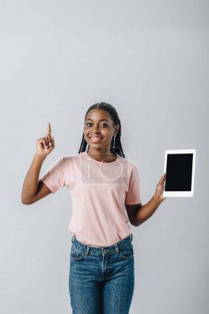 Afrikanerin hält digitales Tablet mit leerem Bildschirm und zeigt Ideenschild isoliert auf grau