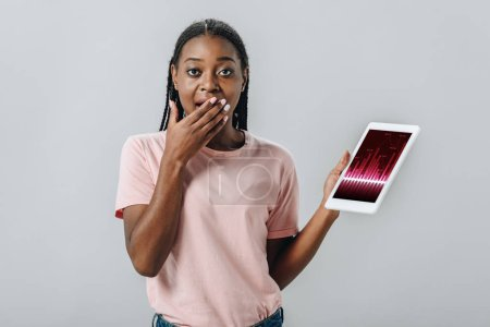 Photo pour Femme afro-américaine tenant une tablette numérique avec des cartes d'affaires et couvrant la bouche avec la main isolée sur gris - image libre de droit