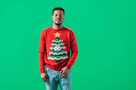 Photo for African American man in Christmas sweater looking at camera isolated on green - Royalty Free Image