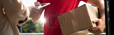 Photo pour Tir panoramique de l'homme de livraison donnant la tablette numérique à la femme - image libre de droit