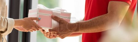 Photo for Panoramic shot of delivery man giving pink present to woman - Royalty Free Image