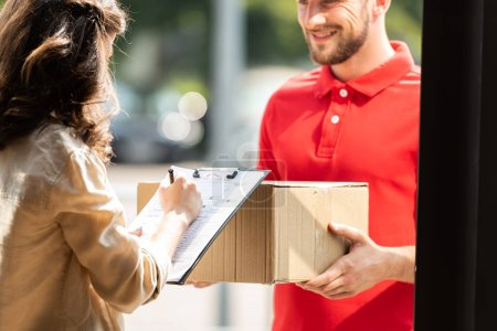 cropped view of happy delivery man holding box near woman with clipboard and pen