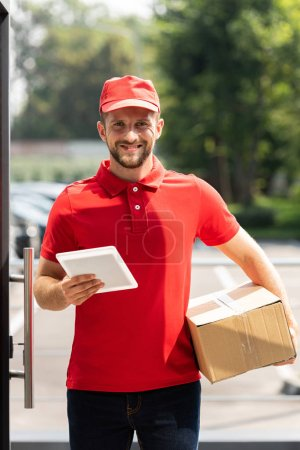 Photo for Happy delivery man holding box and digital tablet - Royalty Free Image