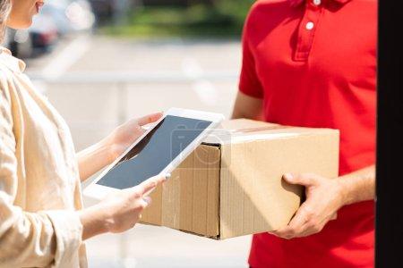 Photo pour Vue recadrée de livraison homme tenant boîte près de la femme avec tablette numérique - image libre de droit