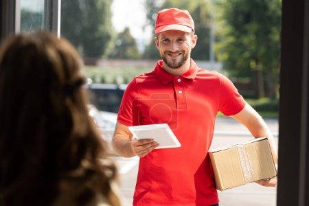 Photo pour Foyer sélectif de l'homme gai de livraison retenant la tablette et la boîte numériques près de la femme - image libre de droit