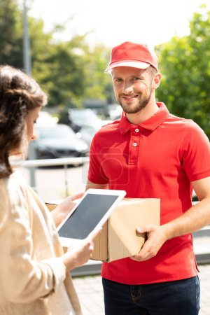 Photo for Selective focus of happy delivery man holding box near woman using digital tablet - Royalty Free Image