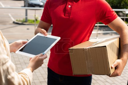 Photo pour Vue recadrée du livreur retenant le paquet près de la femme avec la tablette numérique - image libre de droit