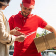 cheerful delivery man gesturing while looking at digital tablet near woman