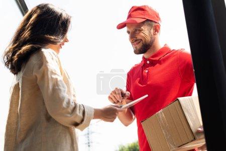 Photo pour Joyeux livreur homme regardant femme avec tablette numérique - image libre de droit