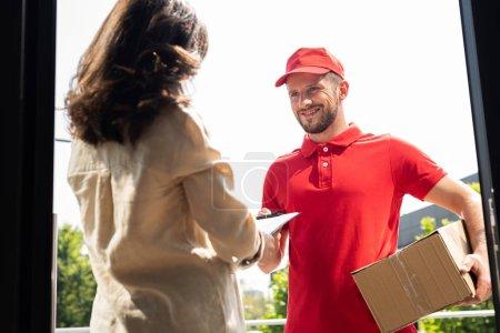 Photo pour Foyer sélectif de l'homme de livraison heureux retenant la boîte et donnant le presse-papiers à la femme - image libre de droit