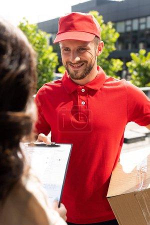 Photo pour Foyer sélectif de l'homme de livraison dans la boîte de maintien de chapeau et regardant la femme - image libre de droit
