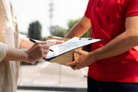 Photo for Cropped view of delivery man holding clipboard while woman signing paper on clipboard - Royalty Free Image